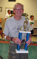 Photo of Dick Wilson holding his trophy for winning the 5K Walk at the Fiesta Mexicana.
