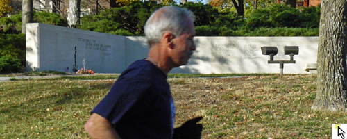 Photo of Ken Baldwin running past the Vietnam War Memorial at the KU Vets Day 5K and link to Flickr slideshow.