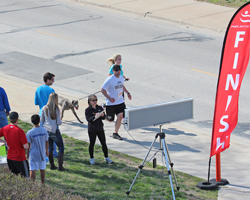 Photo of a couple with their dog finishing the 2013 Race Ipsa 5K.