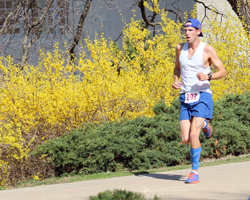 Photo of the lead runner running passed the forsythia in front of Snow Hall.
