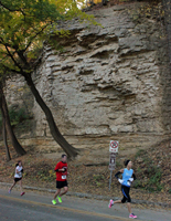 Photo of runners at the Cliff Hanger 8K running by cliffs on Cliff Drive.