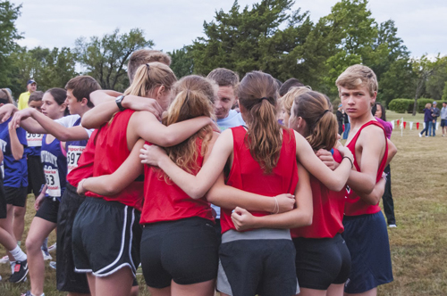 Photo of the team huddle before the start of the Emporia Cross Country Invitational.