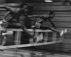 Photo of George Byers in hurdle race at Allen Fieldhouse, Feb 1967